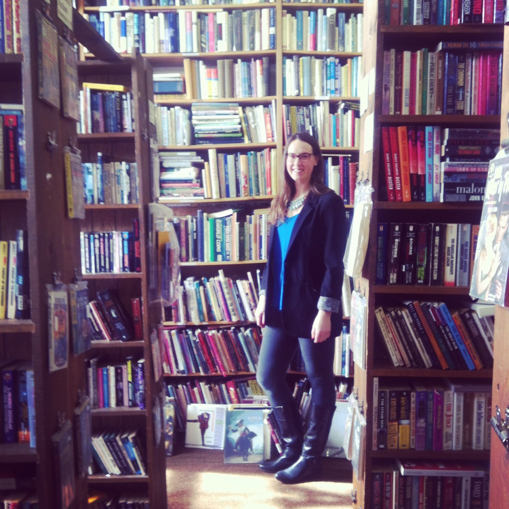 "The Library Diary ""About"" page picture. Woman standing in used book store."