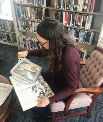 The author of The Library Diary sitting in the reading room at the Boothbay Memorial Library. She is using a reading magnifier to read a book about birds.