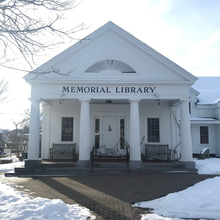 The front of the Boothbay Harbor Memorial Library. A white building with four columns supporting the roof.
