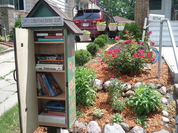 A Little Free Library sitting on the side of the road with its door open, showing shelves of free books to take home.