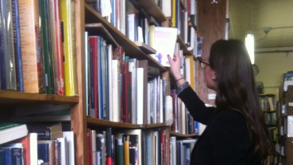 A woman looking at a tall shelf of books, picking one of the shelf to read.