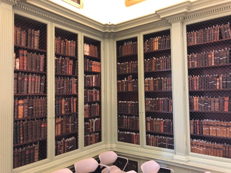 Shelves of books from the original collection of the Redwood Library and Athenaeum in Newport, RI line the walls behind cages in a reading room. Most of the books are from the 1700s.