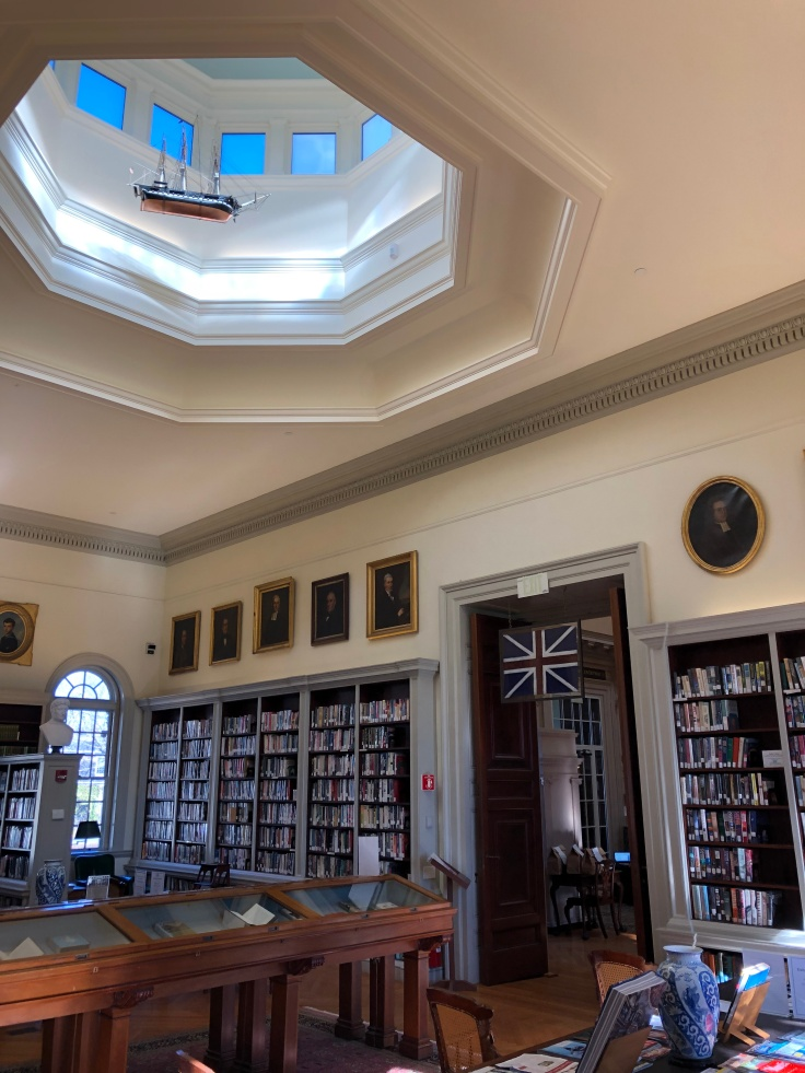 A reading room in the Redwood Library and Athenaeum in Newport, RI. Bookshelves line the walls and the tall ceilings open up into a large skylight in the center.